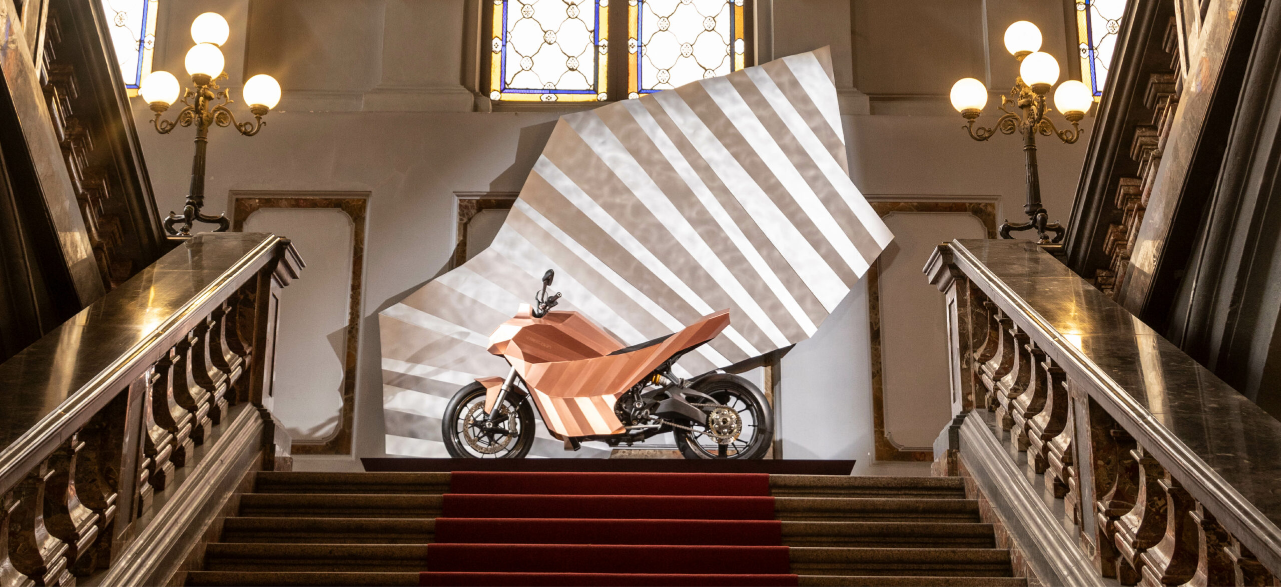 Left side of a standalone copper motorbike built on a Ducati Monster chassis on a quarter landing inside of Litta Palace of Milan, Italy.