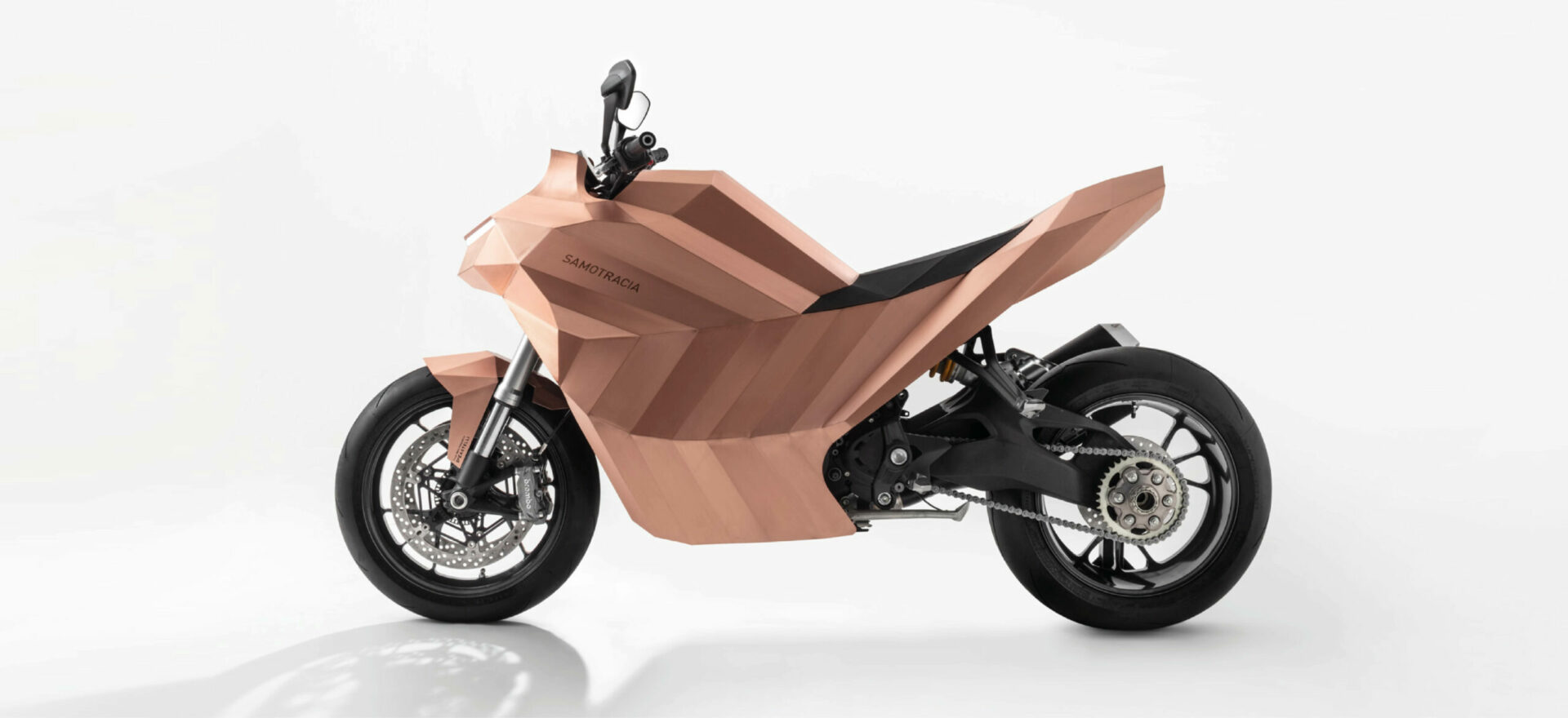 Left side of a standalone copper motorbike built on a Ducati Monster chassis in a white background.