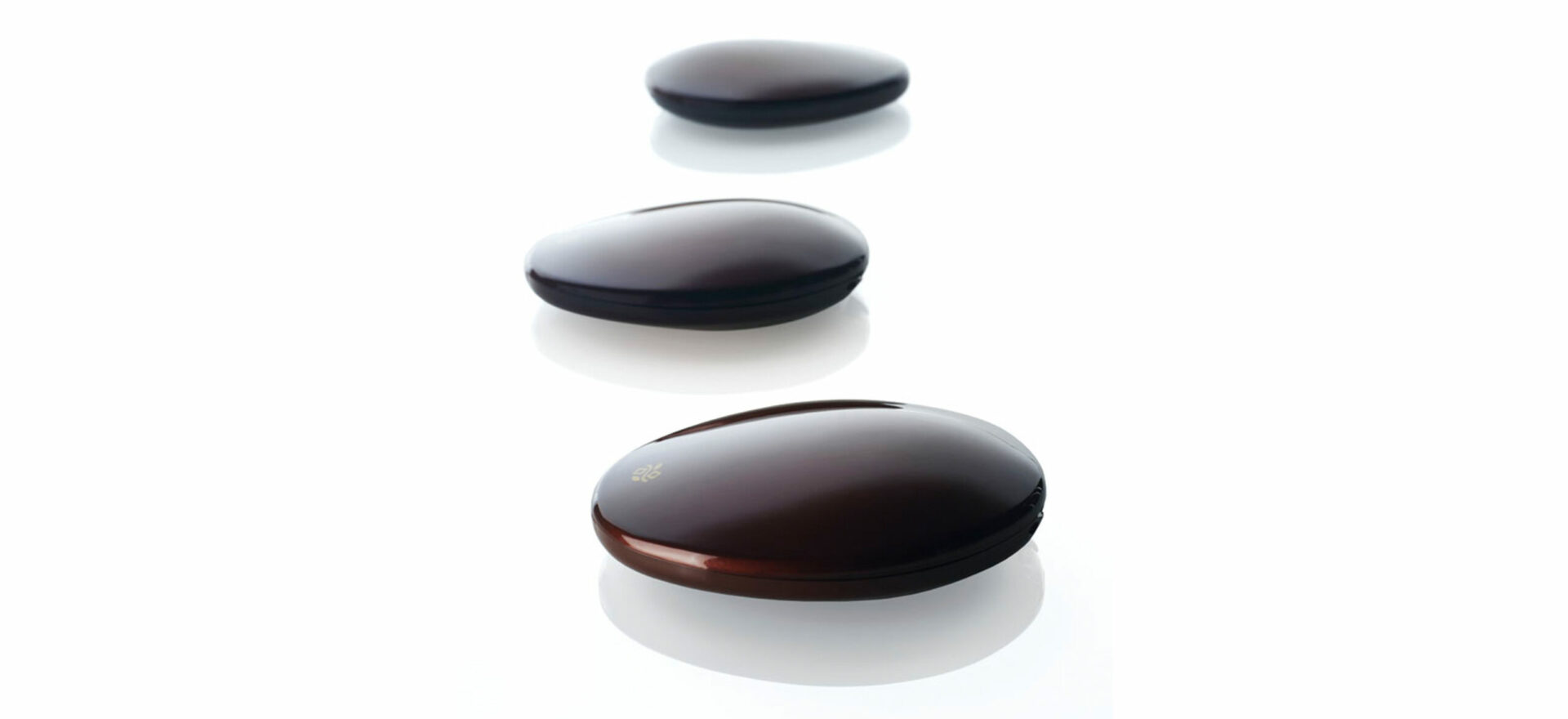 Three packaging of Deborah Milano make up designed with the form of river stones in plastic with a withe background.