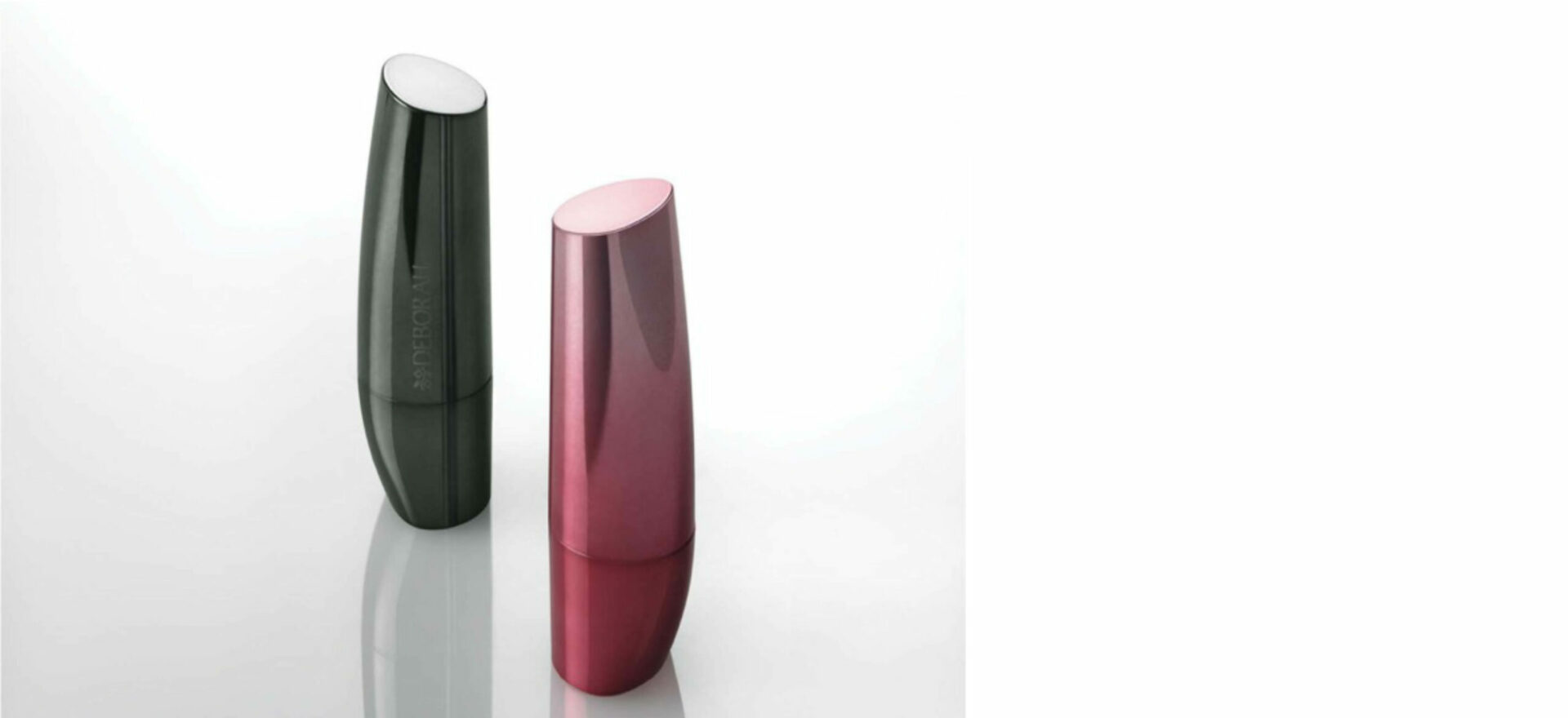 Two lipsticks standing up vertically, one black and one pink in a white background. In 2007 the packaging of the Bioetyc skincare line won the Good Design Award.