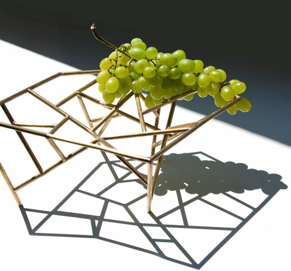 Oggetti Smarritti center piece by Mario Trimarchi holding grapes showing a projection of shadows on the table in an architectural style.