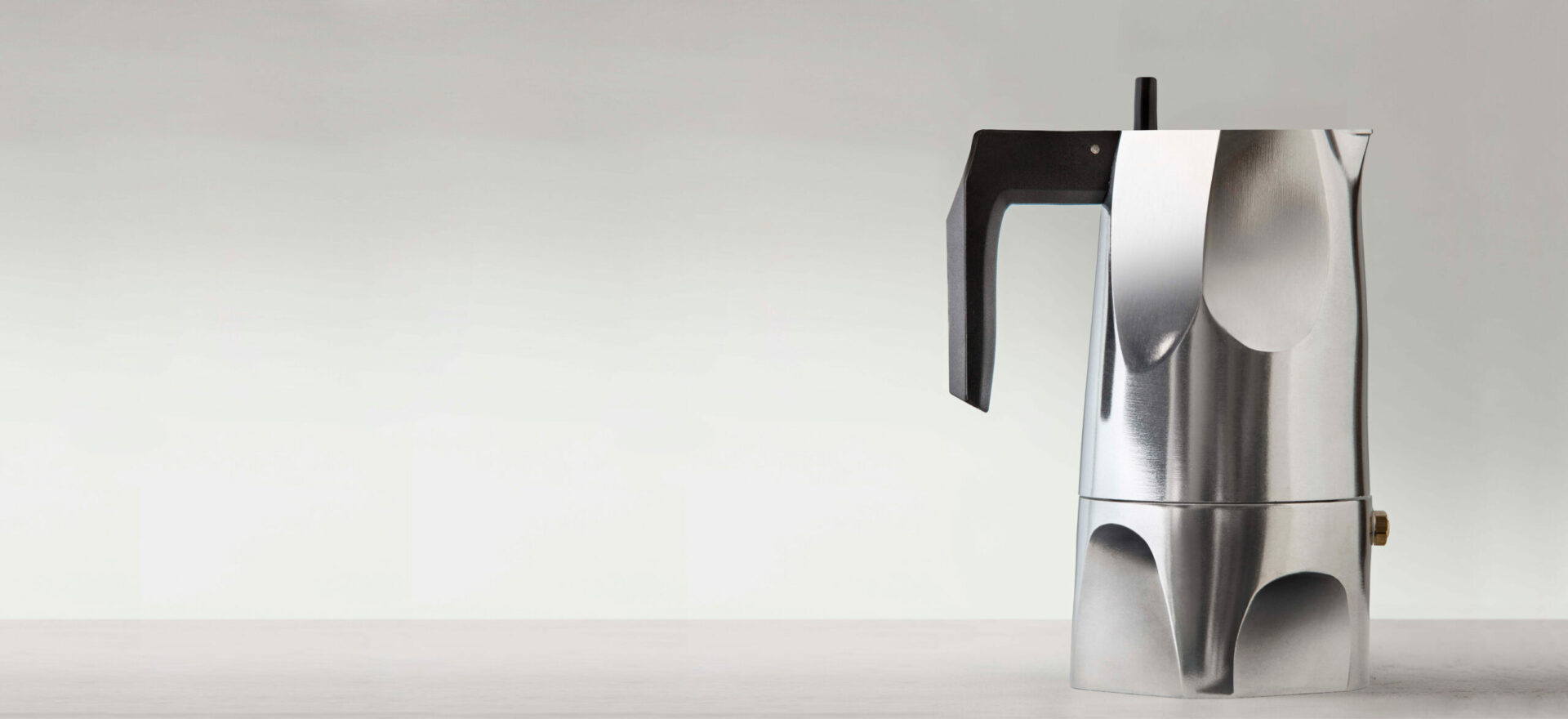 Right side photo of Ossidiana Expresso Coffee maker for Alessi. The model presented in the picture is in aluminium casting with handle in thermoplastic black resin, showing the details of its form inspired in the stone arrowheads handmade by natives.